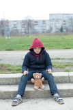 Young homeless boy on the street with bear. The young homeless boy on the street with bear Royalty Free Stock Photo