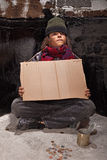 Young homeless boy on the street with a sign. Waiting for charity money stock photography