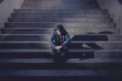 Young homeless man lost in depression sitting on ground street concrete stairs. Young desperate jobless man in casual clothes abandoned lost in depression Stock Photography