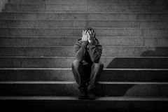 Young homeless man lost in depression sitting on ground street concrete stairs Stock Photo