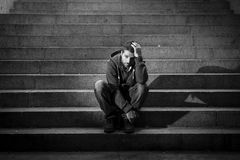 Young homeless man lost in depression sitting on ground street concrete stairs. Young desperate man wearing casual clothes abandoned and lost in desperation and Royalty Free Stock Photography