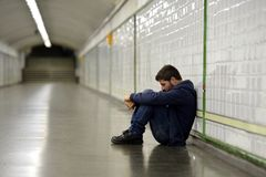 Young homeless man lost in depression sitting on ground street subway tunnel Royalty Free Stock Photo