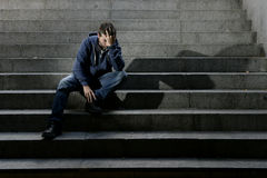 Young homeless man lost job in crisis suffering depression sitting on ground street concrete stairs. Young desperate man in casual clothes abandoned lost in Royalty Free Stock Photo