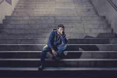 Young homeless man lost job in crisis suffering depression sitting on ground street concrete stairs. Young desperate man in casual clothes abandoned lost in Royalty Free Stock Photos