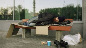 Young Homeless man trying to sleep under jacket on bench at the sidewalk. Young Homeless man trying to sleep under jacket on bench at sidewalk Royalty Free Stock Image