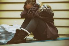 Homeless young teen taking shelter. Young homeless teenage girl finding shelter in the cold winter by an abandoned building Royalty Free Stock Photos