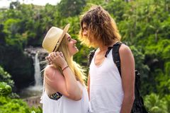 Young honeymoon couple in the jungle on the watefall background. Bali island. royalty free stock photo