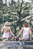 Young honeymoon couple swings in the jungle near the lake, Bali island, Indonesia. royalty free stock image