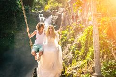 Young honeymoon couple swings in the jungle near the lake, Bali island, Indonesia. royalty free stock images