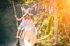 Young honeymoon couple swings in the jungle near the lake, Bali island, Indonesia. stock photos