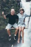 Young honeymoon couple swings in the jungle near the waterfall, Bali island, Indonesia. Ubud. Young honeymoon swings in the jungle near the waterfall, Bali Stock Image