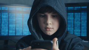 Young hooded hacker kid using a smartphone device to hijack. Genius boy wonder hacks system at cyberspace.