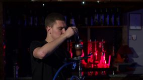 Young hookahman changing the coals in the hookah in a dark. Slow motion. Young hookahman changing the coals in the hookah in a dark shisha lounge. Close-up stock video footage