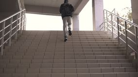 Young hooligan streetstyle guy running up by stairs on the football stadium at the evening at autumn stock footage