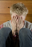 Young hopeless blond  man close eyes by hand. Young hopeless blond man close eyes by hand. Teen`s problem Stock Images