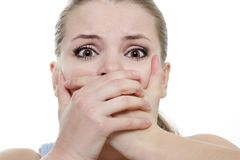Young horrified woman closing her mouth with hands. Over white Royalty Free Stock Photos