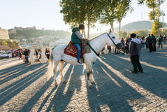 Young horse rider standing in rays of evening sun during autumn city festival Tbilisoba Stock Photo