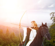 Young horseback girl shooting arrow from bow royalty free stock images