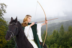 Young horseback girl shooting arrow from bow Royalty Free Stock Photos