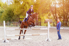Young horseback sportswoman training with trainer Stock Image