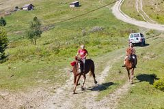 Young horsemen gallop across the Starishora mountain valley, Ukraine. royalty free stock photography