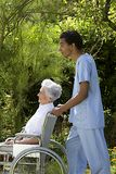 Young Hospital staff happily pushing a senior patient in wheelchair outdoors. Young hospital staff pushing  happy senior patient in wheelchair outdoors Stock Photos