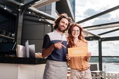 Young hospitality professionals opening nice summer terrace. Opening terrace. Young hospitality professionals feeling excited while opening nice summer terrace royalty free stock image