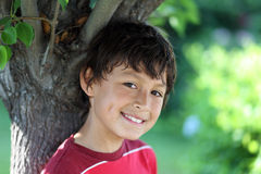 Young hot boy standing under shade. Of a tree in the summer heat Stock Images