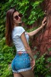 Young hot brunette in mirrored sunglasses and shorts in the Park. Young hot brunette in mirrored sunglasses and shorts with sexy buttocks in the Park Royalty Free Stock Photography