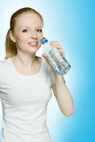 Young hot girl drinking water. Studio shot over blue background Stock Photography