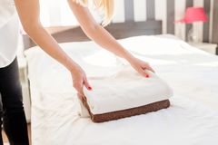 Young hotel maid placing fresh towels on a bed Royalty Free Stock Image