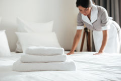 Young hotel maid setting up pillow on bed. Young hotel maid making the bed with clean fresh towels Stock Photography