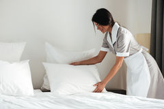 Young hotel maid setting up pillow on bed. Young hotel maid setting up white pillow on bed sheet in hotel room Royalty Free Stock Photography