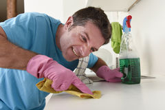 Young house cleaner man washing and cleaning the kitchen tired i. Young house cleaner man washing and cleaning the kitchen with detergent spray bottle and sponge royalty free stock photography