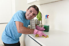 Young house cleaner man washing and cleaning the kitchen tired in stress. Young house cleaner man washing and cleaning the kitchen with detergent spray bottle stock photography