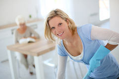 Young housekeeper cleaning home Stock Images