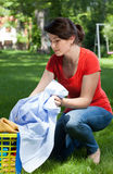 Young housekeeper with laundry outdoors Stock Photos