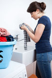 Young housekeeper washing the clothes. Vertical view of a young housekeeper washing the clothes Stock Photo