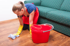 Young housekeeping lady wiping the wooden floor Stock Photos