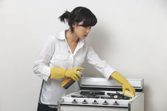 Young housemaid cleaning stove against gray background Royalty Free Stock Images