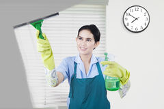 Young housemaid cleans dirty window Stock Photo