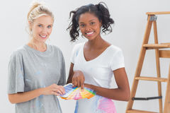 Young housemates choosing colour for wall and looking at camera Royalty Free Stock Photography