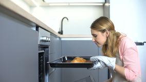 Young housewife in apron taking cookies from oven, smelling baked confection. Stock footage stock footage