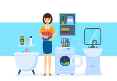 Young housewife in bathroom, lays the things in washing machine. Royalty Free Stock Photography