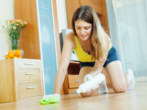 Young housewife caring for parquet. Floor with furniture polish at home stock photos