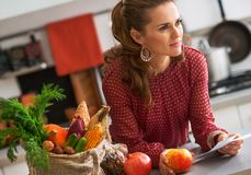 Young housewife with checks after grocery shopping Royalty Free Stock Image