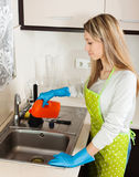 Young housewife cleaning pipe with detergent Royalty Free Stock Photo
