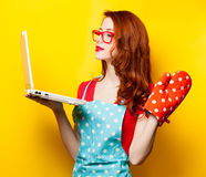 Young housewife with computer and oven gloves. On yellow background Stock Photography