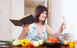 Young housewife  with cookery book Stock Photos