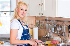 Young Housewife is cooking and chopping onions Royalty Free Stock Photography